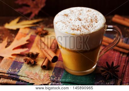 Pumpkin spiced latte or coffee in a glass on a vintage table. Autumn or winter hot drink.