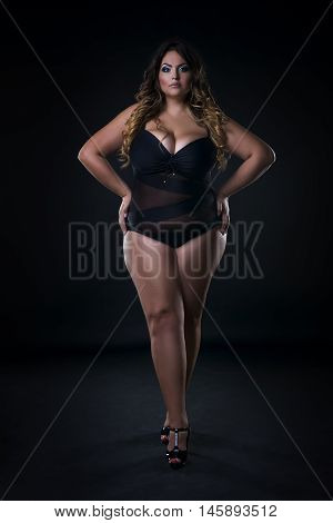 Young beautiful caucasian plus size model in swimsuit xxl woman on black background full length portrait