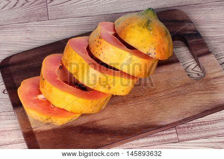Sliced sweet papaya on butcher served. Side view.