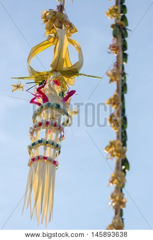 Bali Penjors, decorated bamboo poles along the village street in Bali, Indonesia. Penjors are placed outside Balinese Hindu homes during religious holidays such as Galungan and Kuningan