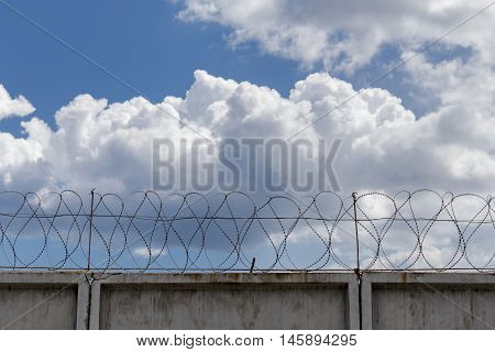 Fence with barbed wire on the background of clouds.