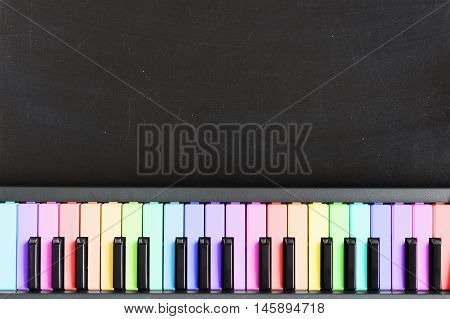 Colorful music keyboard on blackboard background for music school children with copy space