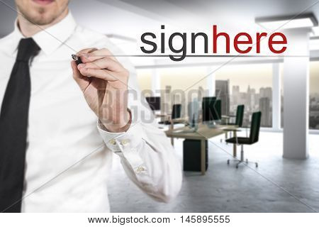 businessman in modern office writing in the air sign here