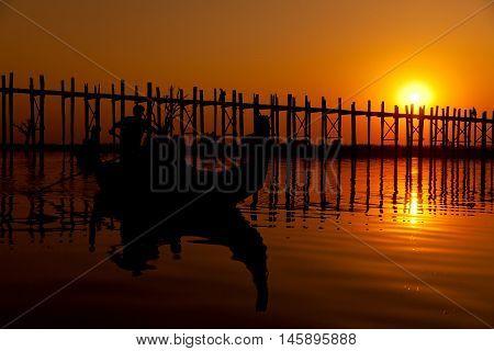 U Bein Bridge at sunset with people crossing Ayeyarwady River Mandalay Myanmar