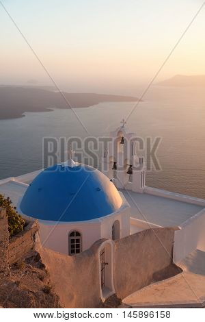 Famous church in Fira Santorini at dust with a perfect view of the volcano.