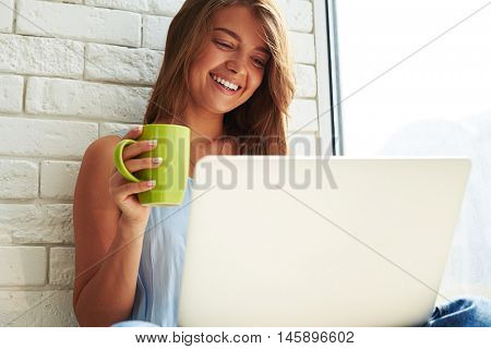An attractive girl has rather warm news on her laptop