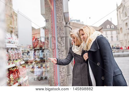 Two beautiful women, mother and daughter, window shopping in historical centre of the city of Vienna, Austria. Winter. Woman pointing at somoething with finger.