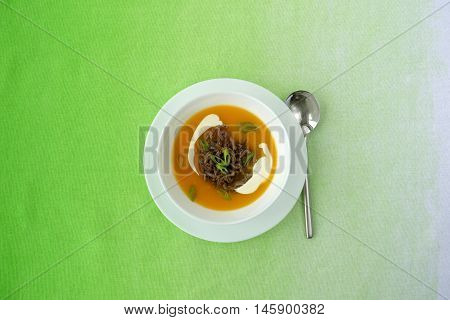 Homemade Pumpkin Soup with fried minced meat sour cream and spring onions on modern bright lime green fading background. Served in a white porcelain soup bowl and a soup spoon on the side.