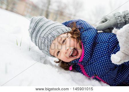 Cute little girl in blue jacket and knitted hat playing outside in winter nature, lying on the ground