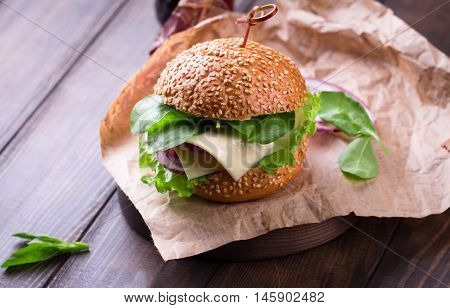 Delicious cheeseburger with salad ingredients served on a craft paper on a rustic wooden table