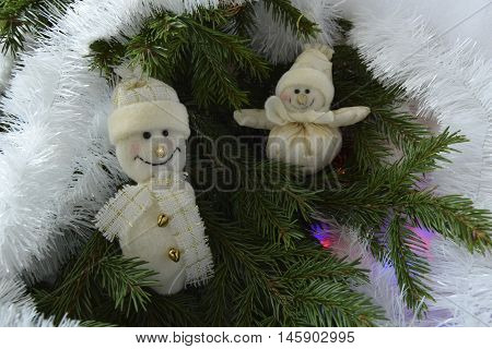 Christmas toys in the form of snowmen. Toys are located on a fir-tree. Snowmen are dressed in a scarf and a cap.