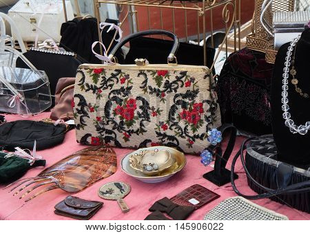 Stand with vintage embroidered purse costume jewelry and more at flea market