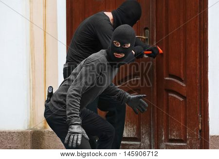 Armed thieves breaking a door