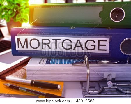 Blue Office Folder with Inscription Mortgage on Office Desktop with Office Supplies and Modern Laptop. Mortgage Business Concept on Blurred Background. Mortgage - Toned Image. 3D.