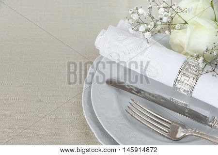 Beautiful decorated table with empty white plates linen lacy napkin cutlery and white rose flowers on tablecloths with space for text