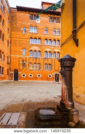 A small Square Adriano with red-brick building in Venetian style with a well in Venice. Italy