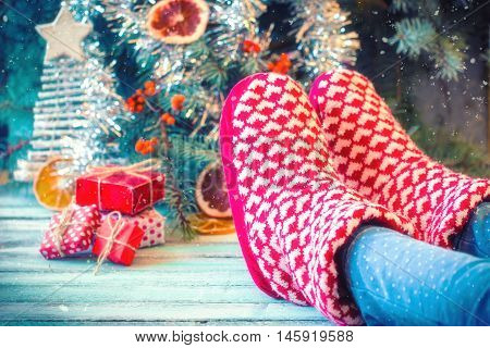 Woman relaxes her feet in woollen socks. Close up on feet. Winter and Christmas holidays concept.Vintage filtersoft focus