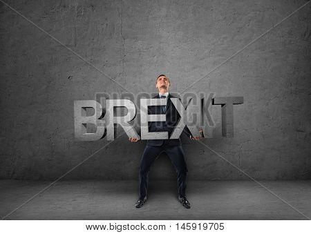 Businessman holding heavy 3d 'brexit' word in hands. British withdrawal. Significant decision. Substantial choice. Europe and United Kingdom. Difficulties and doubts.
