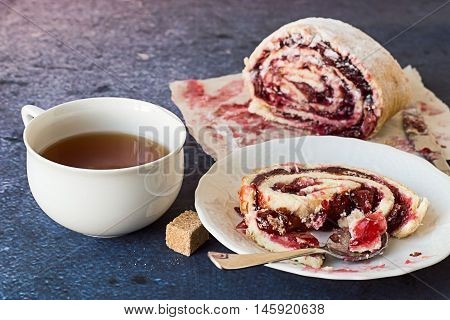 Dessert. Roll filled with cherry filling on a dessert plate and on paper, beside a cup of tea.
