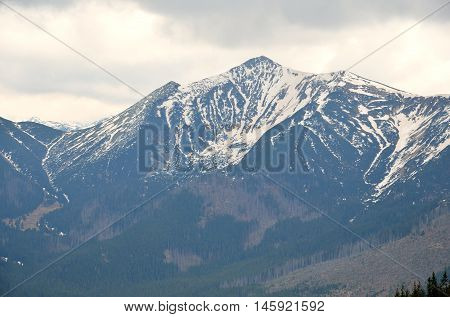 Spring cloudy mountain landscape. Mountain snowy peak in the clouds in Western Tatra Poland.