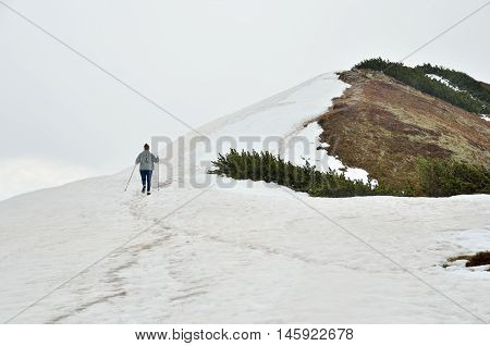 Spring cloudy mountain landscape. The tourist on a snowy mountain trail in Western Tatra Poland.