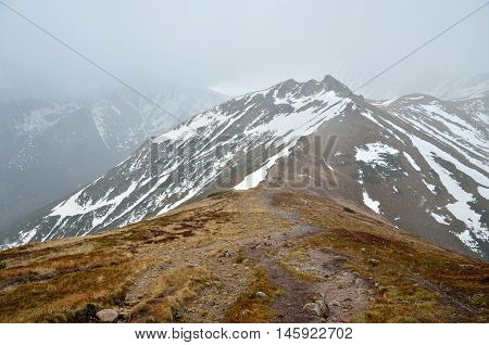 Spring cloudy mountain landscape. Patches of snow on mountain peaks in Western Tatra Poland.
