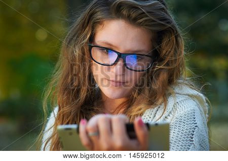 beautiful young woman in glasses with the tablet in the autumn park.