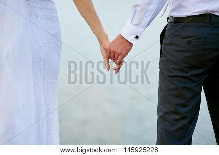 Wedding photo of bride and groom holding hands close up
