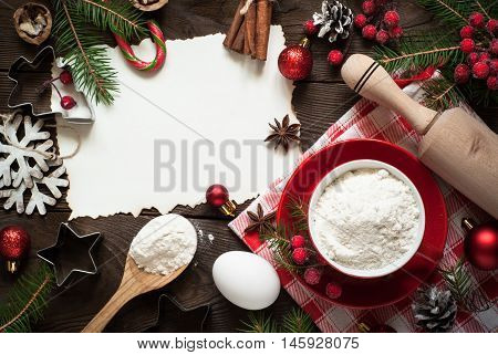 Ingredients for cooking christmas baking - flour egg spices and cookie cutters. Space for text.