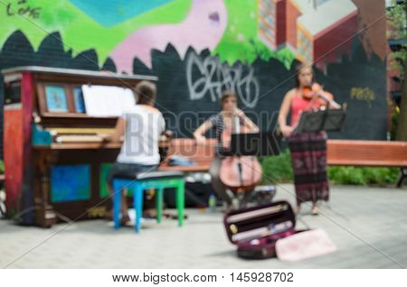 MONTREAL CANADA JUNE 22 2016: Defocused view of street musicians playing outdoors at free piano in Montreal