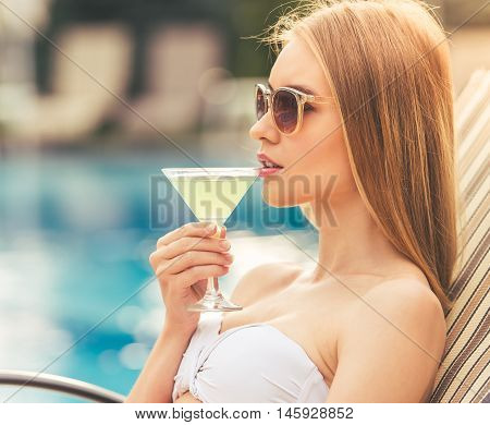 Attractive girl in white swimwear and sun glasses is drinking a cocktail and sunbathing while lying on the chaise longue near the pool