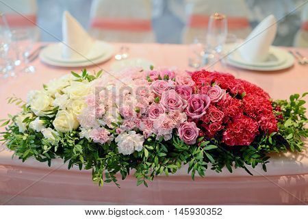 Beautiful wedding restaurant for marriage. White decor for bride and groom. Colorful decoration for celebration. Beauty bridal interior. Bouquet food and flowers in hall