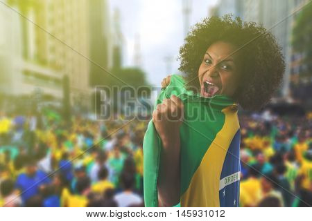 Woman holding the flag of Brazil in Sao Paulo