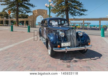 NAPIER NEW ZEALAND - MARCH 8 2013: Vintage Packard Promenades Tour car in front of The New Napier Arch and Veronica Sun Bay on Marine Parade providing guided tours to tourists around the Art Deco district and waterfront