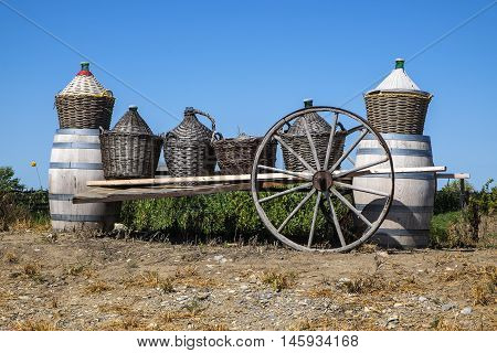 Wine Barrels and Big Bottles of Wine in Baskets on a Wagon