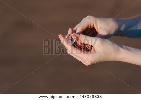 Ice cubes in human hands. Girl holding ice cubes in his hands outdoors. Brown background in the background. Ice melts in your hands.