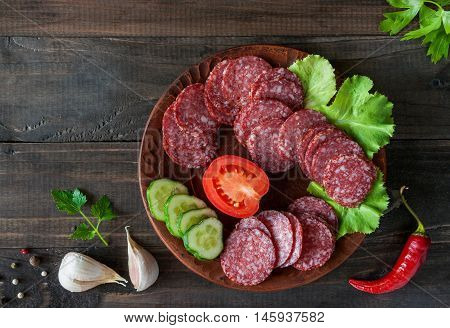 Slices of salami with vegetables and spices on wooden background
