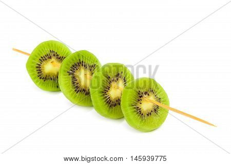 Slices of kiwi fruit on a wooden skewer isolated on white background.