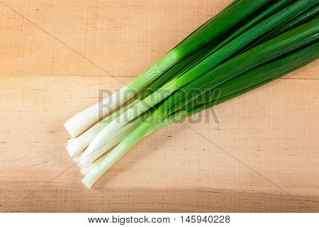 Fresh green onions on a wooden board.