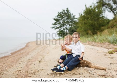 Two brothers sitting on a bank of the river