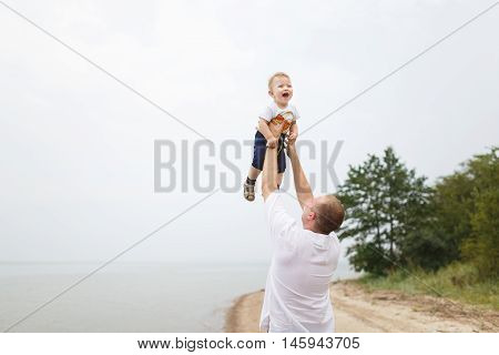 Father playing with his little son on a bank of the river