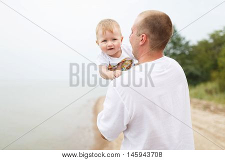 Father hugging his little son on a bank of the river