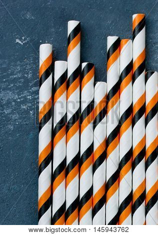 Halloween straws for drinks. Striped drink straws on a gray stone background