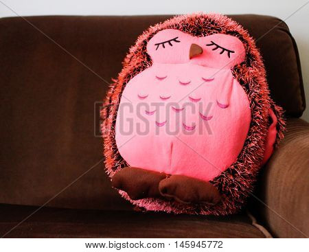 cute pink stuffed owl on brown couch