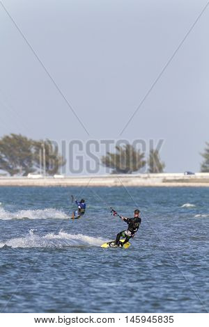 Tampa Bay Florida USA - February 28 2011: Kiteboarders race across Tampa Bay on breezy afternoon