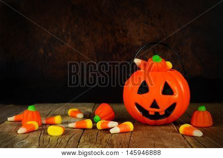 Halloween Jack O Lantern Candy Holder With Scattered Candy On Rustic Wood With Orange And Black Back