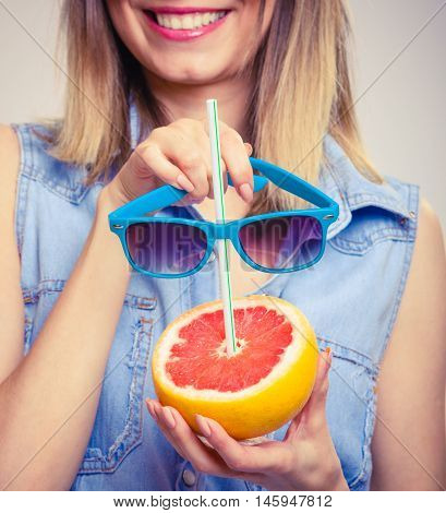 Summer girl holding grapefruit drink. Happy tourist enjoyed vacation.