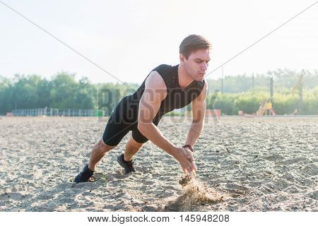 Fit man doing clapping push-ups during training exercise workout on beach in summer