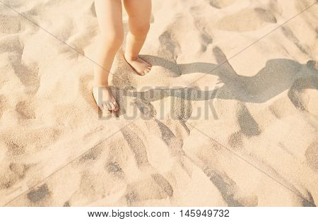 Baby Girl Child Feet In Sand Beach? Child Playing In White Beach Sand In Sunny Day. Sandy Feet On Th