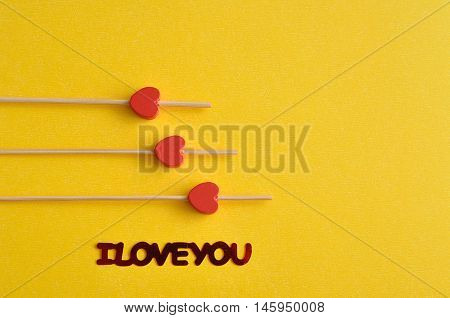 Valentine's Day. Three red hearts on sticks with a yellow background an I love you in red lettering